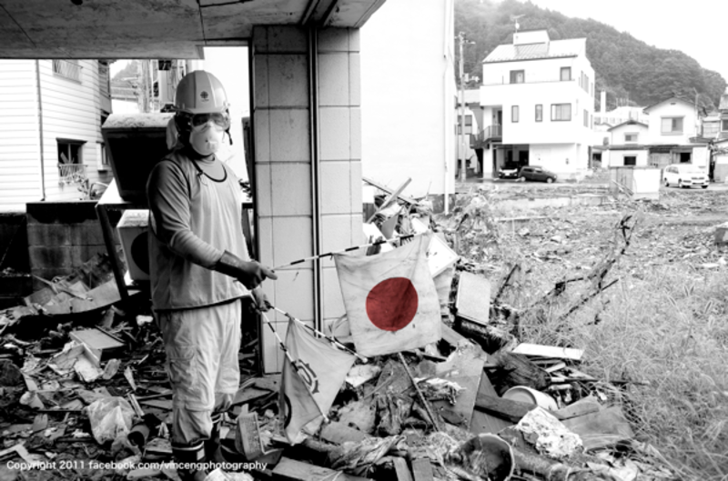 A volunteer holds up a flag found in the rubble of Kamaishi City. Photograph © 2011 by Vince Ng